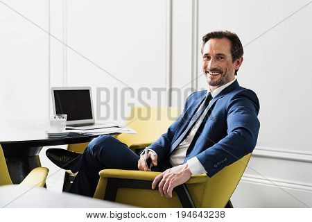 I like my job. Portrait of excited middle-aged businessman sitting with comfort in his new office. He is holding cellphone and laughing