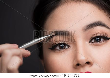 Close up of beautiful face of young asian woman getting make-up. The artist is applying eyeshadow on her eyebrow with brush