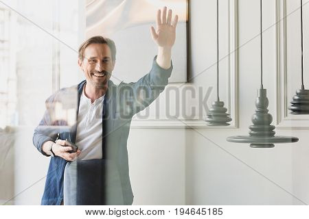 Hello. Waist up portrait of happy senior man waving arm to someone through glass wall. He is holding smartphone and laughing. Copy space in right side