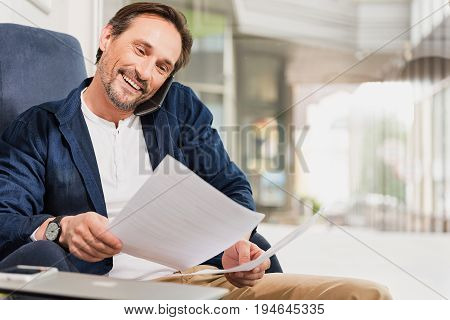 Portrait of happy businessman reading documents while talking on mobile phone. He is sitting on armchair with comfort and laughing. Copy space