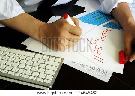 Trader is writing buy or sell in a note.