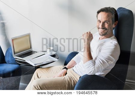 Portrait of happy man is satisfied with his business. He is sitting near open portable computer in cafeteria. Man is looking at camera and laughing
