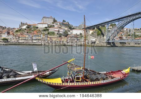 PORTO, PORTUGAL - AUGUST 7, 2015: Traditional wooden boats at the Douro river for transporting wine with the bridge Dom Luis and the city in the background in Porto Portugal