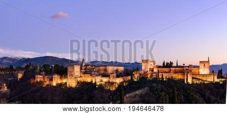 Alhambra fortress night view against Sierra Nevada mountains, Granada, Spain