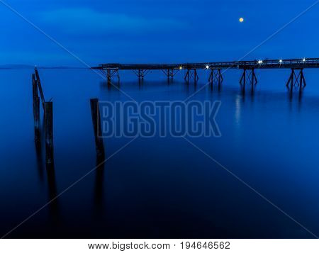 Moon rises over the fishing pier in Sidney Vancouver Island British Columbia