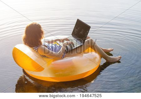 Freelancer Works On A Laptop Sitting In An Inflatable Ring In The Water, Free Space. Business Woman