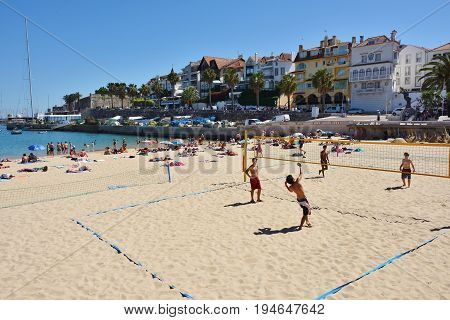 CASCAIS PORTUGAL - JUNE 7 2017: People sunbathing on the Praia Ribeira public beach. Cascais is famous and popular summer vacation spot for Portuguese and foreign tourists