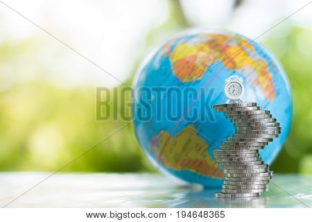 A globe with a map of the world behind a white clock on the stack of coins. money financial and business growth concept.