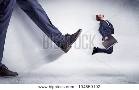 Giant leg kicking small businessman and he is flying away
