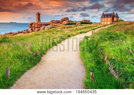 Stunning sunset with lighthouse of Ploumanach Mean Ruz in Perros-Guirec on Pink Granite Coast Brittany France Europe poster