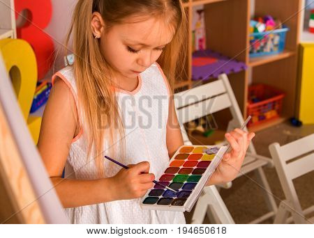 Small student girl painting in art school class. Child drawing by watercolor paints on easel. Kid in orphanage. Craft drawing education develops creative abilities of children.