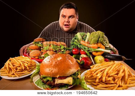 Diet fat man who makes choice between healthy and unhealthy food . Overweight male with hamburgers, french fries and vegetables trays trying to lose weight first time .Wide angle shooting.