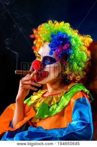 Evil clown on black background. Mad woman is smoking cigar. Portrait of crazy female with an angry look after performance. Female person hates her job.