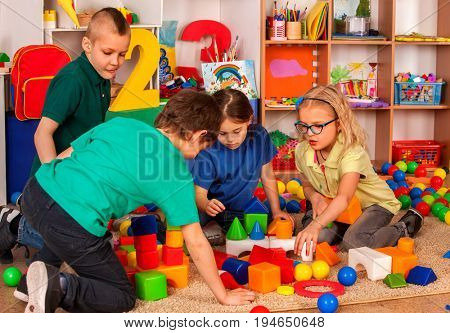 Children building blocks in kindergarten. Group kids playing toy on floor in interior preschool. Little ones develop their fingers in game of cubes.