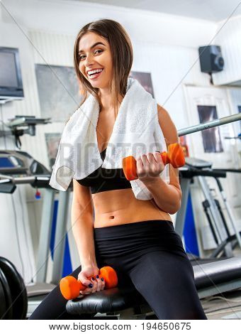 Woman holding dumbbell workout at gym. Weights for women. Middle section of bare belly. Set of heavy dumbbells on background. Body that you want concept. Girl flirts with visitors.
