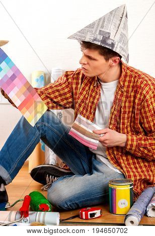 Repair home man holding paint bank. Tired and frustrated mad male in newspaper cap renovation apartment. Worker-builder student with color guide. Choice materials for construction he was in quandary