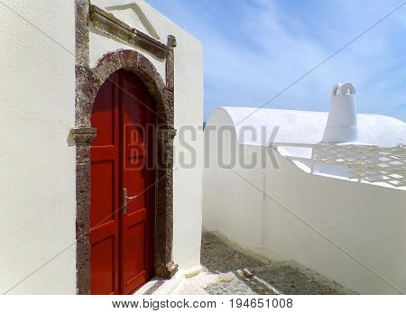 Impressive Greek Style Door Casing with Deep Red Door on Pure White Building at Santorini, Greece