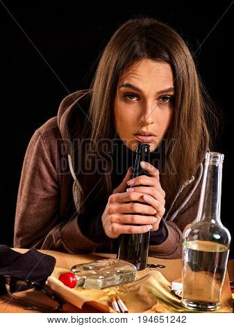 Woman alcoholism is social problem. Female drinking is cause of poor health. Table with empty bottle. Morning after student's party on black background. Temporary memory loss.