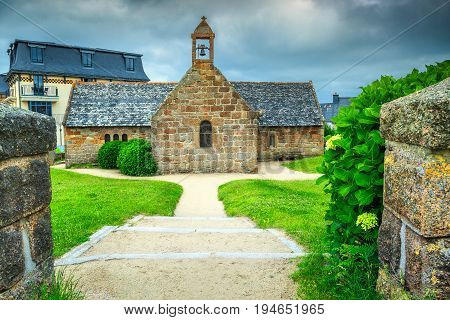 Typical stone chapel in garden with hydrangea flowers Perros-Guirec Brittany France