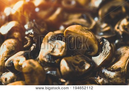 Fried in a frying pan mushrooms champignons closeup background