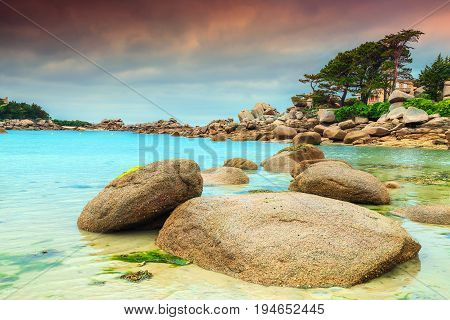Stunning rocky beach with pink granite stones and wonderful green gardens on the coast Ploumanach Perros-Guirec Pink Granite Coast Brittany France Europe