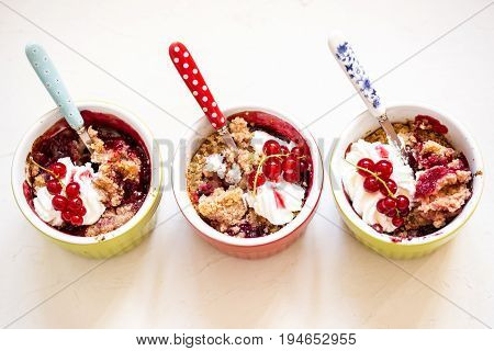 crumble with fresh berries currants cherries strawberries and whipped cream