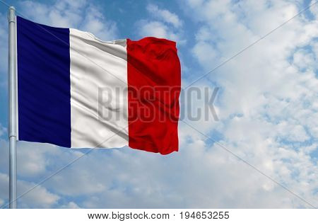 National flag of France on a flagpole in front of blue sky.