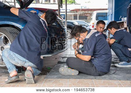 Checking A Car Headlight For Repair At Car Garage
