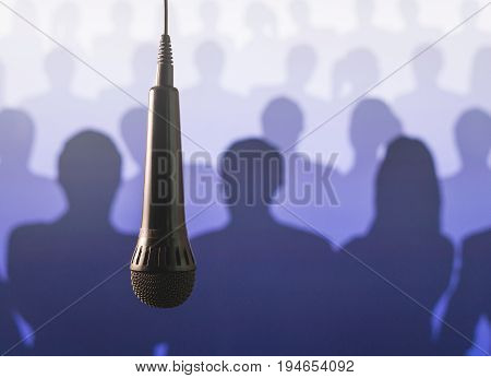 Public speaking and giving speech. Singing to mic in karaoke or talent show background. Close up of microphone hanging from ceiling from wire in front of a crowd of silhouette people.