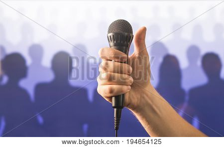 Hand holding microphone and showing thumbs up in front of a crowd of silhouette people. Public speaking and giving speech concept. Singing well live to mic, good karaoke or successful talent show.