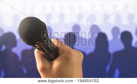 Public speaking and giving speech concept. Close up of hand holding microphone in front of a crowd of silhouette people. Singing to mic in karaoke or talent show concept.