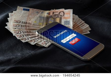 Mobile banking hack and cyber security concept. Hacker and criminal login to persons online bank application and steal money from account. Smartphone and a lot of 50 euro bills.