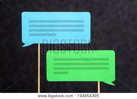 2 chat bubbles and speech balloons having discussion. Modern communication and conversation concept. Mobile and smartphone communication design made from cardboard and wooden stick.