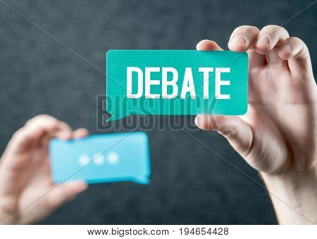 Debate, argument, controversy and disputation concept. Learning to be better speaker. Education to improve dialog. Tell opinions and thoughts in public. Hands holding cardboard speech bubble.