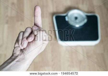Hand showing middle finger to weight scale. Flipping the bird. Man frustrated and angry from being overweight and obese. Problem and failure in weight loss. No results and unsuccessful person.