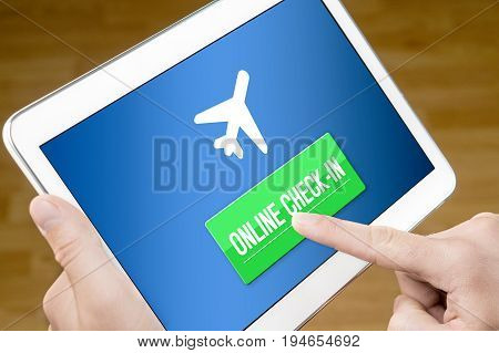 Online check in with mobile device at home. Man checking in to flight with tablet on the web. Internet self service provided by airline.
