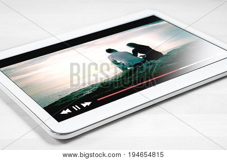 Online movie stream with mobile device. White tablet on wooden table with imaginary video player and film streaming service.