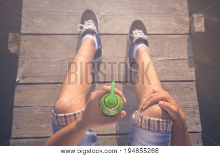 Top down viewpoint of man sitting on pier and holding glass of fresh kiwi juice with drinking straw