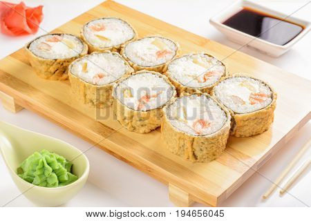 Sushi rolls on a wooden board with soy sauce wasabi and ginger.