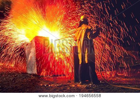 Industrial worker causing shower of sparks, back view