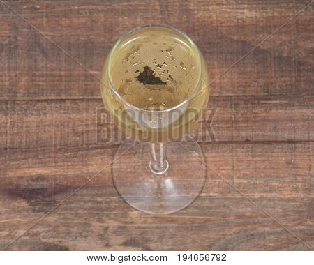 Glass of white wine on vintage wooden background