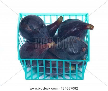 Fresh ripe organic figs in green plastic basket isolated on white background