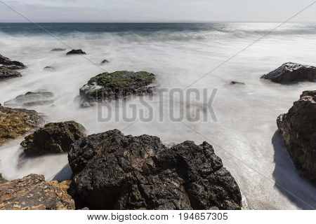 Malibu coast rocks with motion blur water at Point Dume near Los Angeles California.
