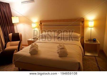 VIENNA, AUSTRIA - APR 30th, 2017: King sized bed in a luxury hotel room with an lounge chair at the Penthouse Suite at the Hilton Vienna.