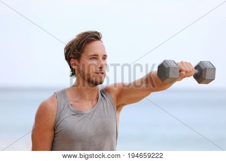 Fitness man lifting dumbbells on beach doing Front Dumbbell Raise i.e. Alternating Front Raise workout for shoulders. Exercising male fitness model working out on beach.