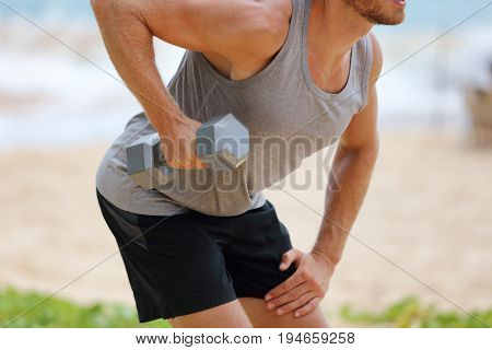 Bent Over Dumbbell Row Exercise - fitness man doing standing row exercise with one free weight. Bent-over Dumbbell Row or Bent over row. Person exercising on beach outdoors.