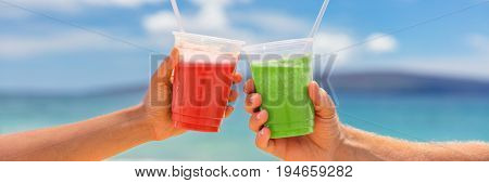 Healthy juice smoothie drinking couple toasting banner. Two fruit juices plastic cups of berry fruits or beets and green vegetable or kiwi smoothies on summer outdoors background.