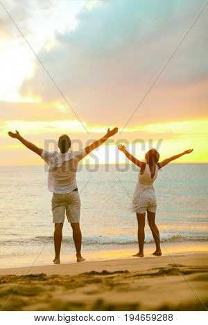 Sunset beach couple praising freedom with open arms up to the sky in success. Mindfulness, spirituality, faith, carefree people winning with raised hands concept.