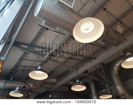industrial ceiling with vents and hanging illuminated lights