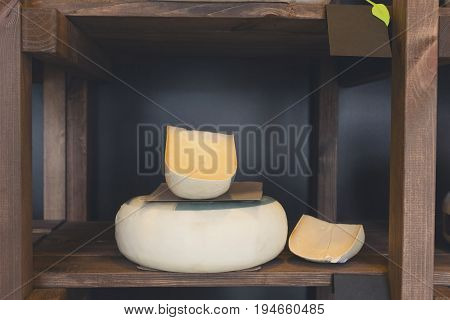 Hard aged cheese in wheel and piece on grocery shop wooden shelf, closeup